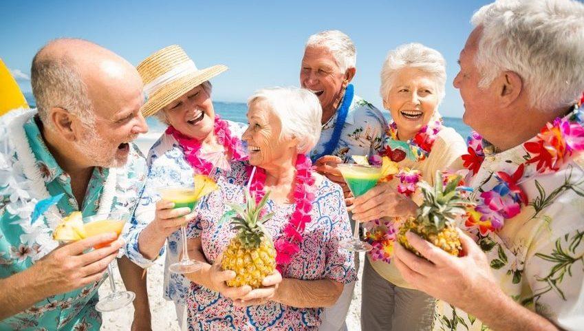 Rüstige Rentner auf Reisen mit Hula-Blumenkränzen und Cocktails mit Schirmchen