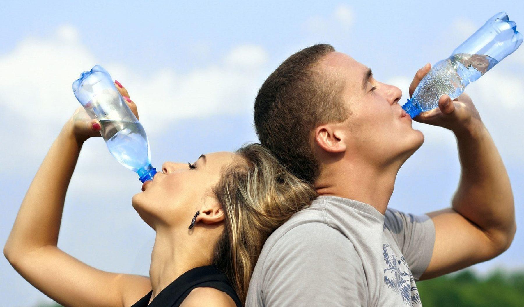 junges Paar trinkt aus Mineralwasserflaschen