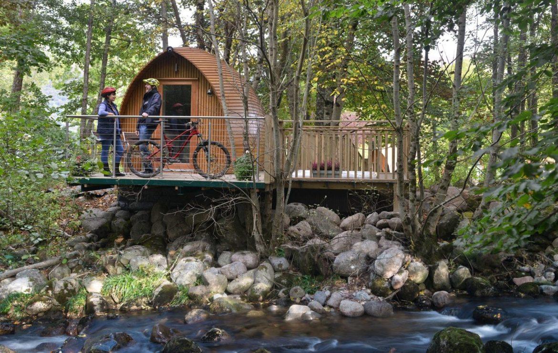 Schönes Holzhaus direkt am Fluss mit zwei Mountainbikern