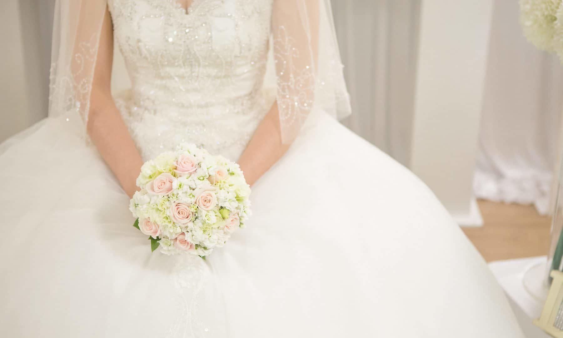 sitzende Braut mit Hochzeitsstrauss auf dem Schoß