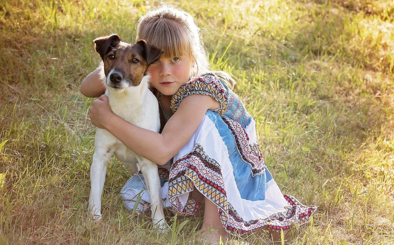 kleines Mädchen auf einer Wiese mit Ihrem Hund im Arm