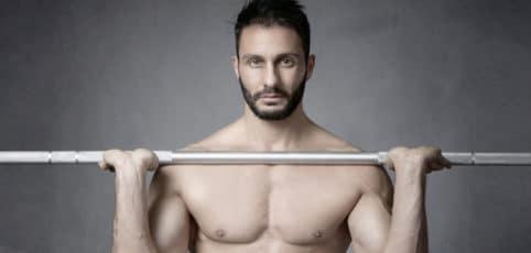 Mann mit nacktem Oberkörper und Sixpack mit Gewichtsstange in Händen