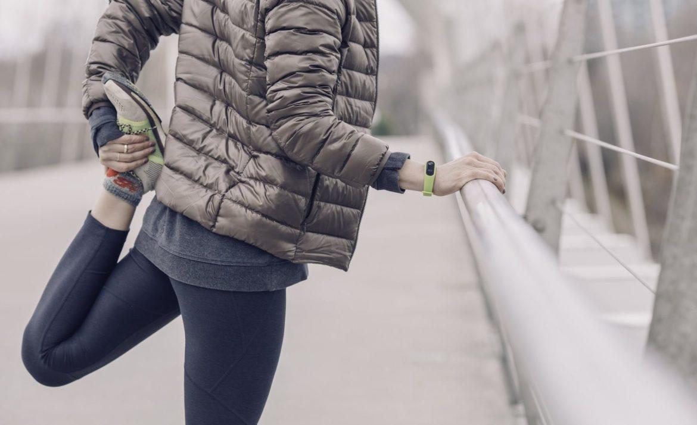 Eine Frau macht einen Warm-Up am Brückengeländer vor dem Laufen