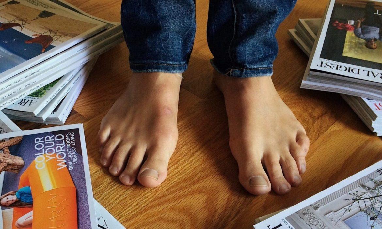 Mann steht mit nackten Füßen zwischen Magazinen