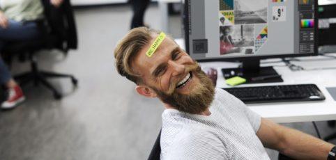 Lächelnder Mann mit Bart im Büro mit Kollegen
