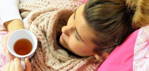 jung Frau mit Erkältung, dickem Schal um den Hals, liegt auf dem Sofa mit einer Tasse Tee