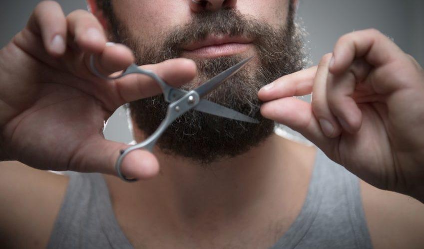 Mann stutzt seinen Bart mit einer Schere