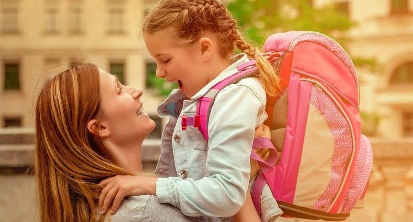 Mutter hebt ihre Tochter hoch samt Schulranzen