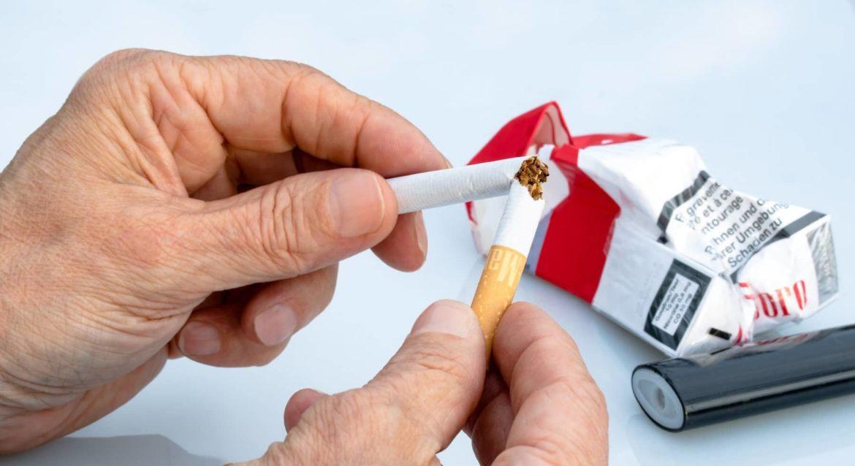 Mann zerbricht seine Zigarette und zerknüllt seine Zigarettenpackung, will das Rauchen aufhören