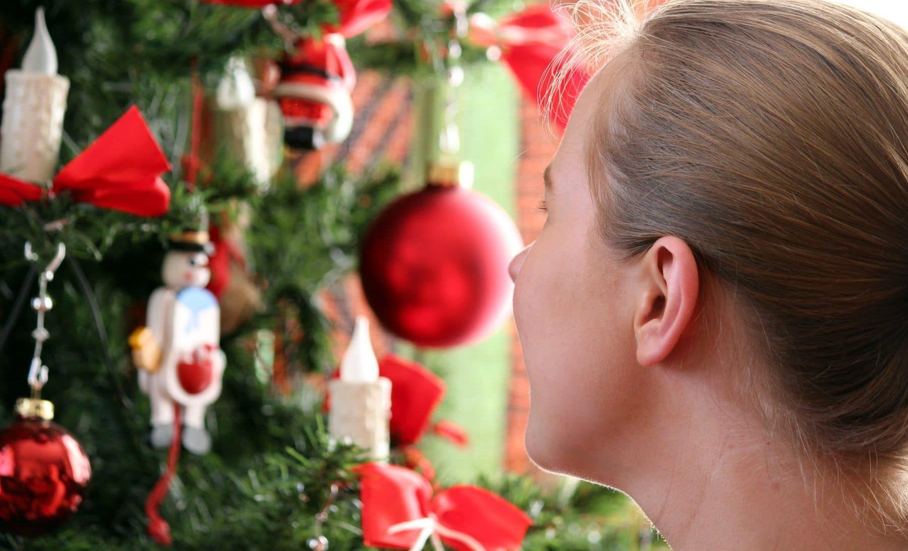 Mädchen schaut geschmückten Weihnachtsbaum an