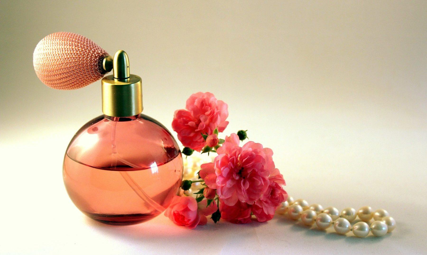 Parfümflacon neben Rosenblüten und eine Perlenkette