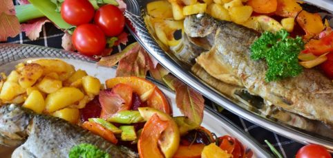 Tisch mit bunten gesottenem Gemüse und gebratenem Fisch