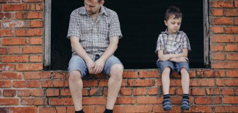 Trauriger Mann und Sohn auf einer Mauer sitzend