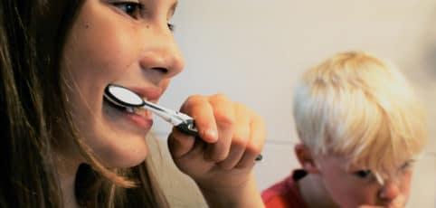 Junge Frau sieht in die Kamera zieht aber ihren Pulli über den Mund