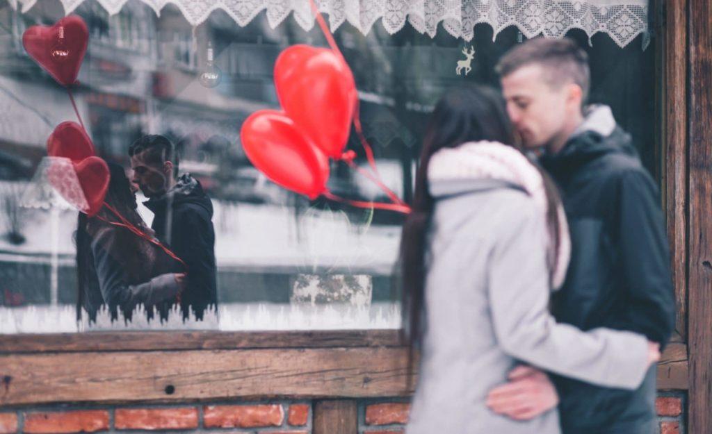 Einfache Liebesgeschenke: Sich küssendes Paar mit roten Herzballons