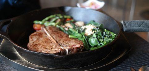 Gusseisenpfanne in Aktion mit Steak und Gemüse