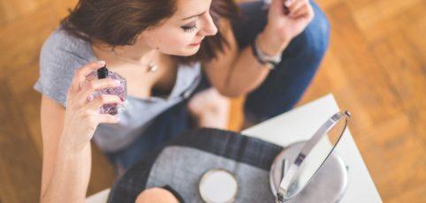 Frau sitzt vor einem Spiegel, macht sich fein und sprüht gerade Parfüm auf ihren Hals