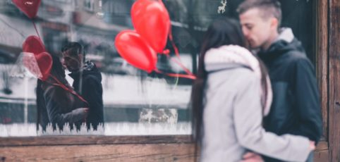 Sich küssendes Paar mit roten Herzballons