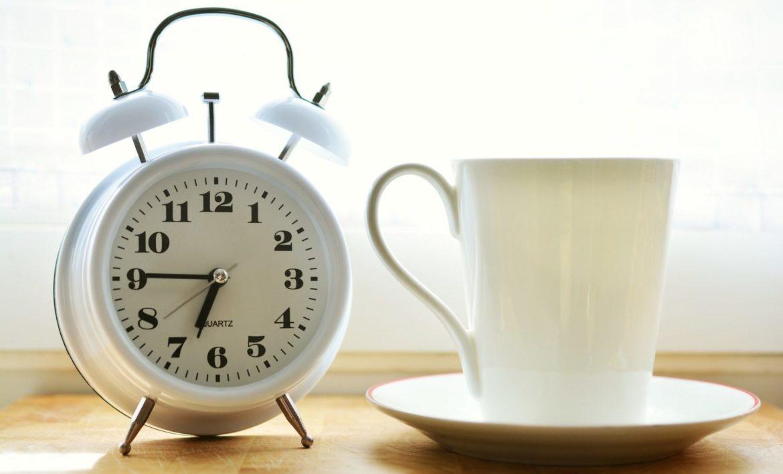 ein Wecker und eine Tasse Kaffee morgens