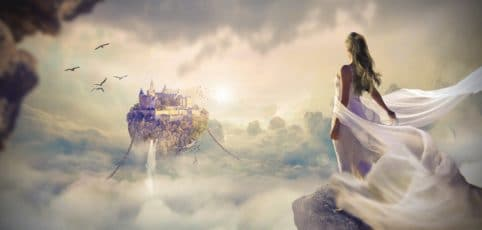 Frau in wallendem weißen Kleid in einer Traumwelt über den Wolken