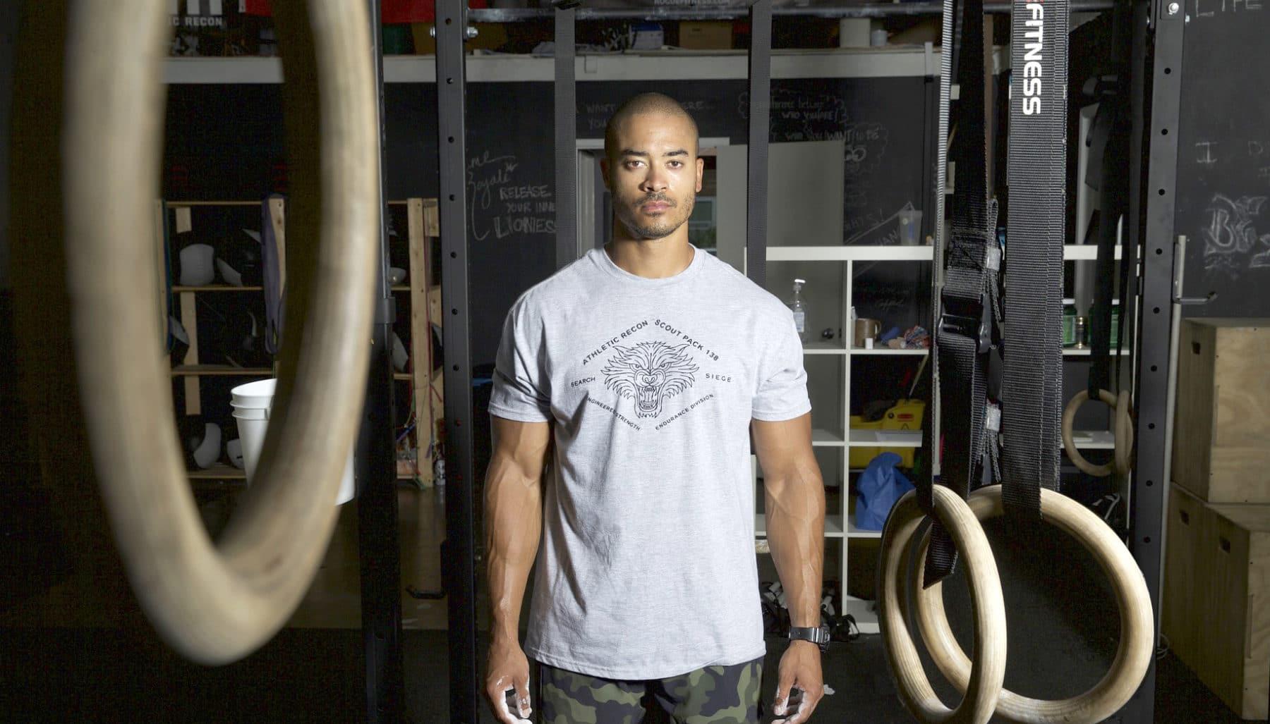 junger Mann im eigenen Fitnessraum und vor Turnringen