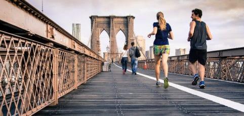 Junge Leute joggen über eine Brücke