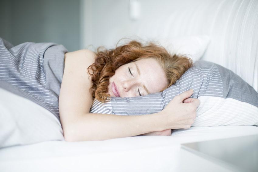 Junge Frau schlafend in Bett auf weißem Kissen