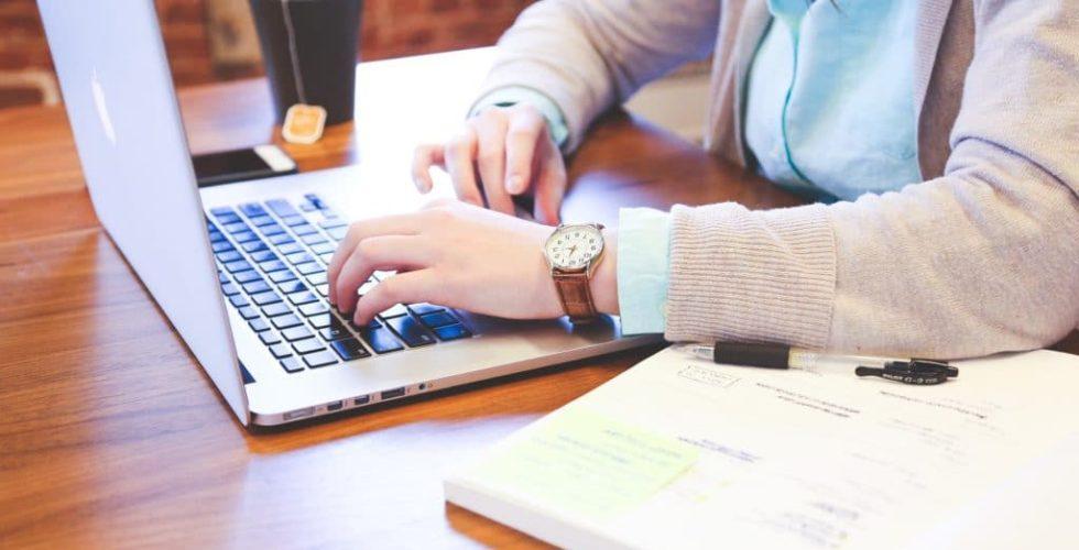Mann tippt auf einer Laptop-Tastatur