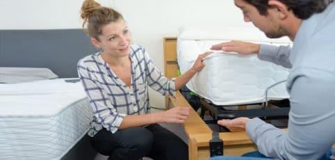 Frau beim Kauf einer Matratze im Gespräch mit dem Verkäufer