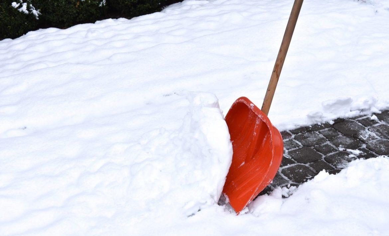 rote Schneeschaufel beim Schnee schieben am Gehsteig