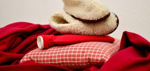 Wärmflasche, Körnerkissen und Kuschelschuhe auf einer roten Decke