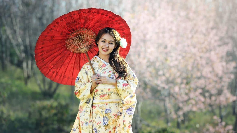 Asiatische schöne Frau in traditionellem Gewand und rotem Schirm