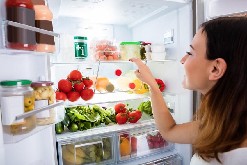 Frau steht vorm offenen Kühlschrank mit Notfalldose drin