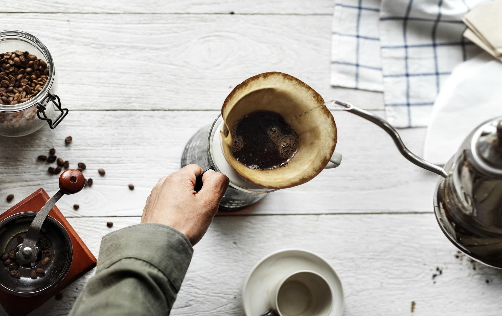 Mann brüht Kaffee mit Filter auf