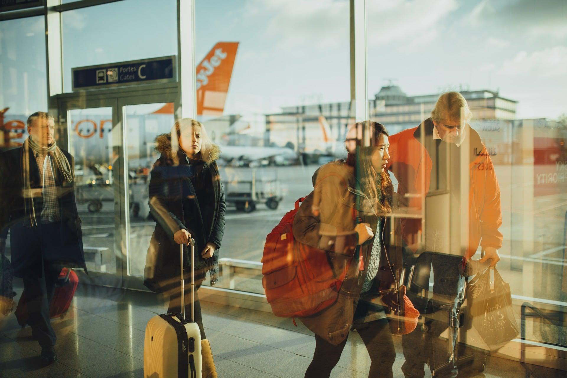 Reisende am Airport mit Gepäck