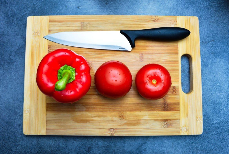 Küchenbrett aus Holz mit Paprika und Tomaten drauf zum schneiden