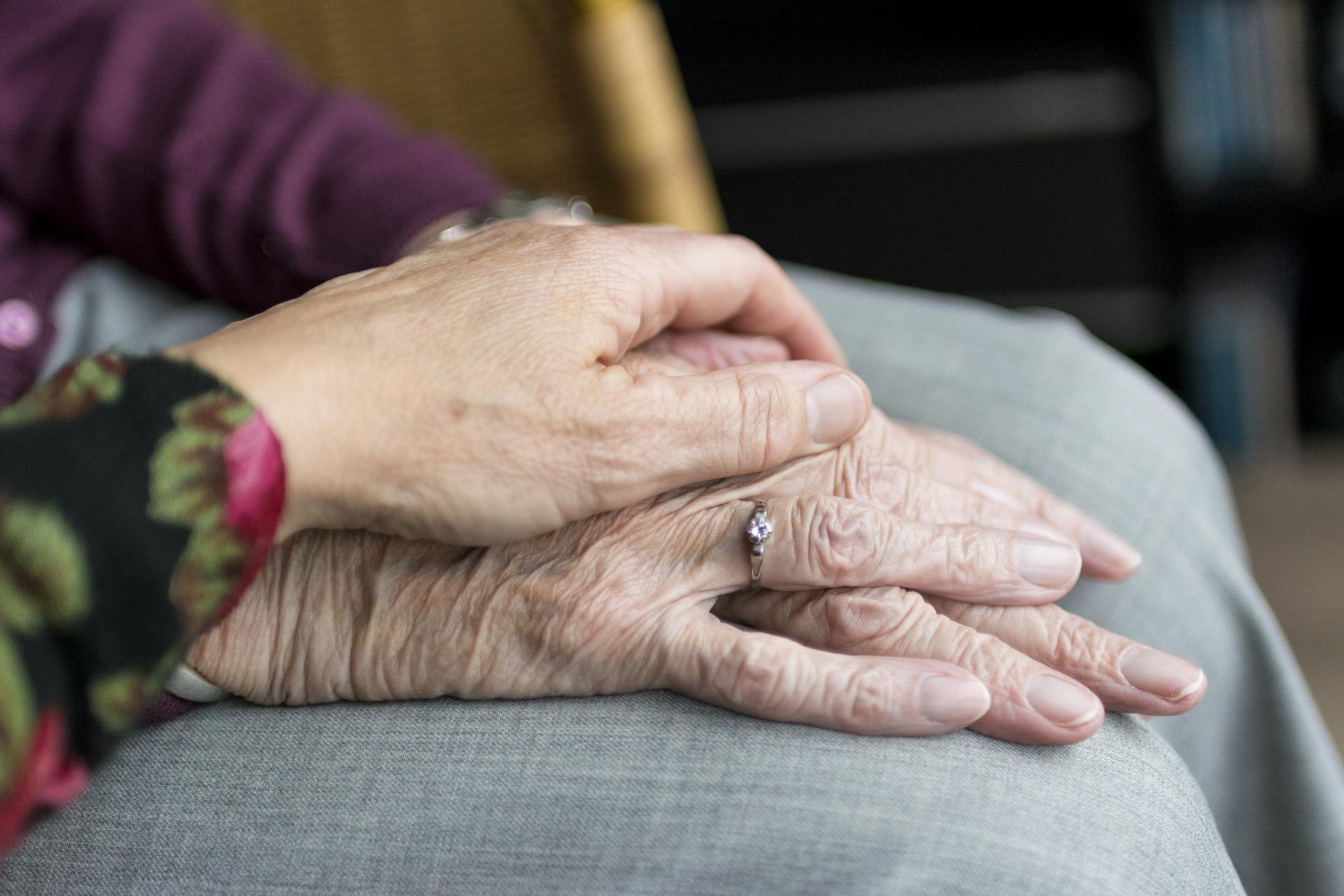 Pflegerin hält die Hand ihrer Seniorin