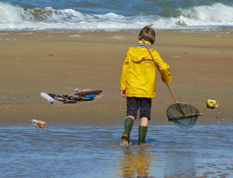 Kind am Strand und Plastikmüll einsammeln