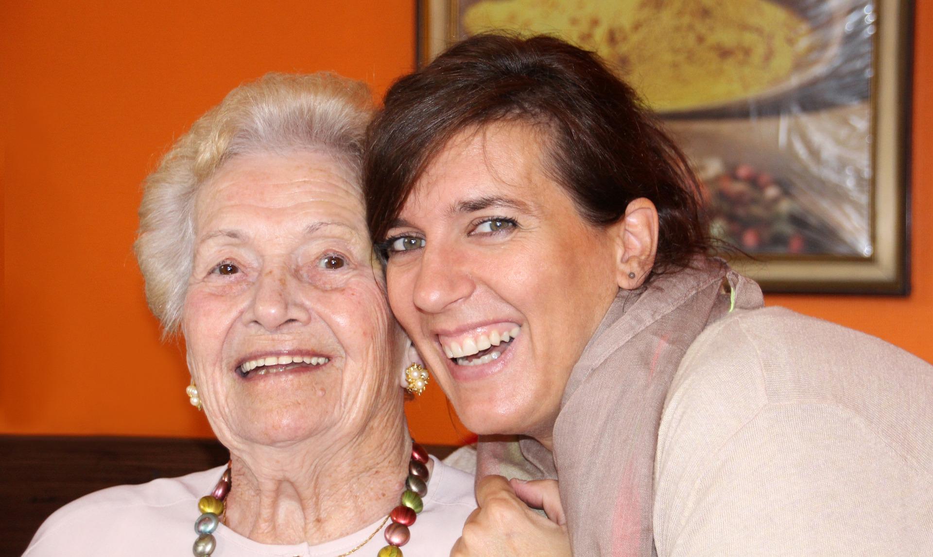 Alte Frau mit Pflegerin in die Kamera lächelnd