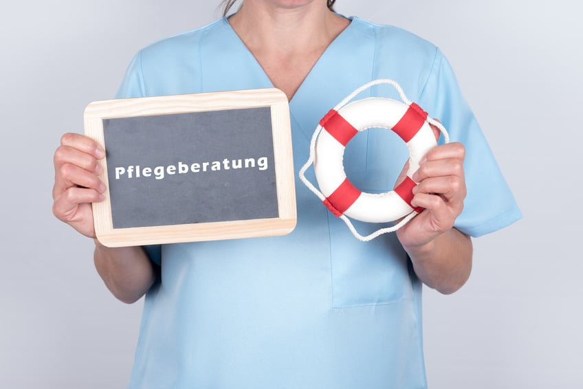 Frau hält Schild mit Aufschrift Pflegeberatung und einen kleinen Rettungsring