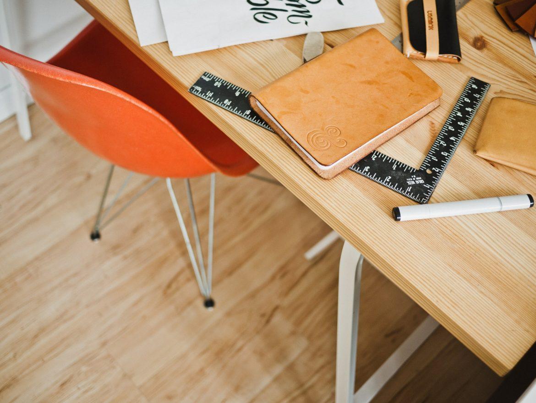 Schreibtisch mit Utensilien und orangenem Bürostuhl