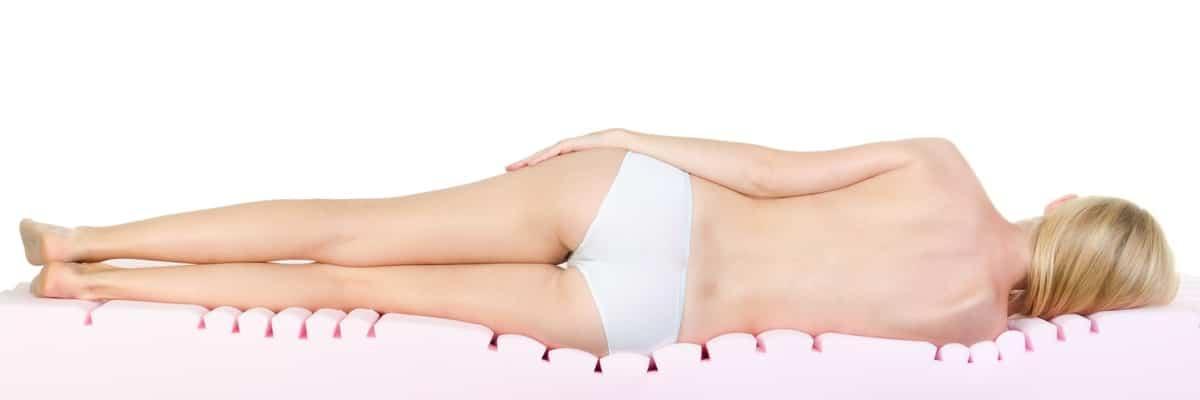Schlafende Frau von hinten auf einer Kaltschaummatratze liegend