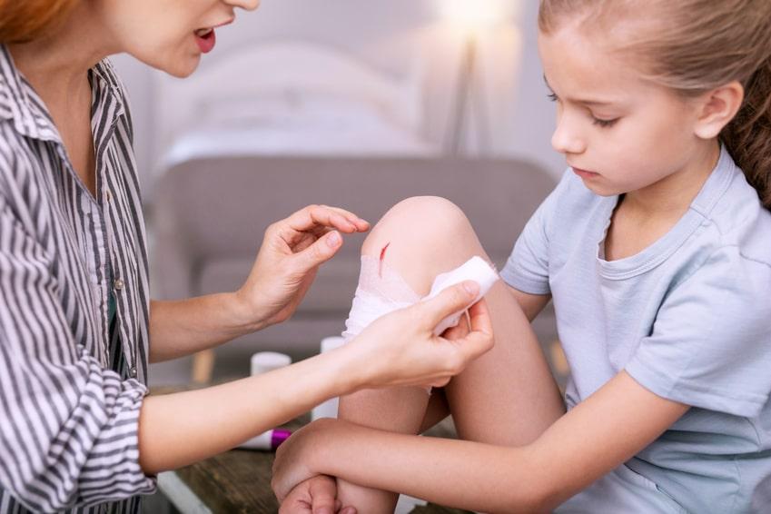 Mutter versorgt verletztes Knie von Tochter