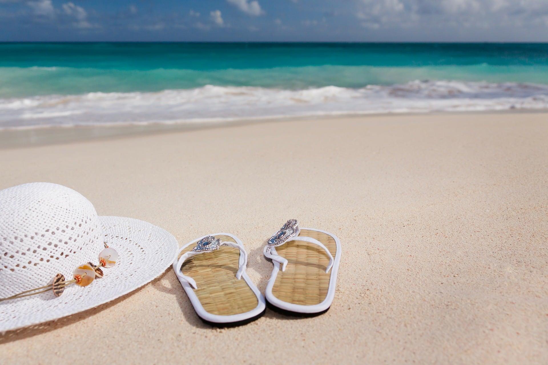 vegan Schuhe am Strand mit Sonnenhut