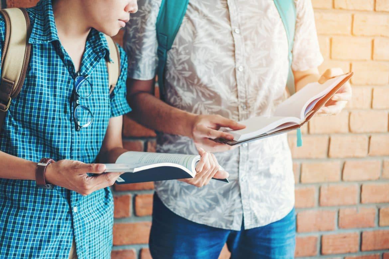 Zwei junge Männer mit Büchern am diskutieren
