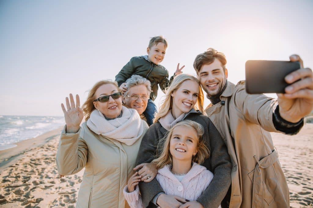 Familie am Strand mit Großeltern und Kindern machen ein Selfie