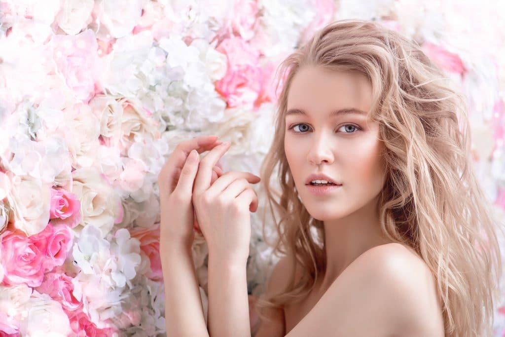 wunderschöne blonde Frau vor einer Rosenwand