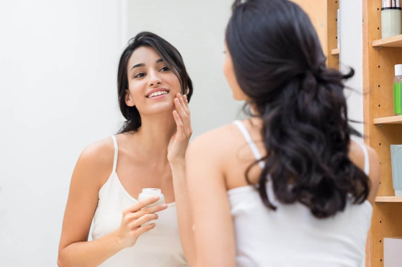 junge Frau vorm Spiegel am eincremen
