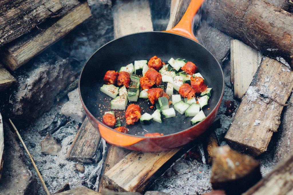 Eisenpfanne auf dem Lagerfeuer mit Gemüse