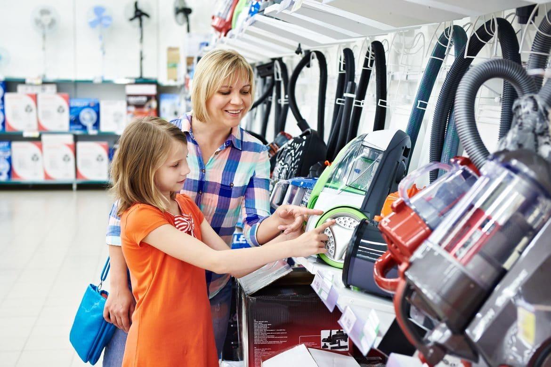Mutter beim Kauf eines Staubsaugers mit ihrer Tochter